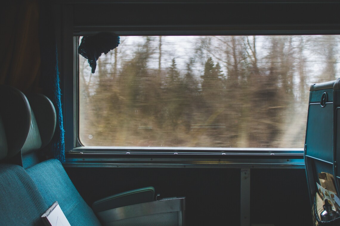 Empty overnight train seats with scenery passing by