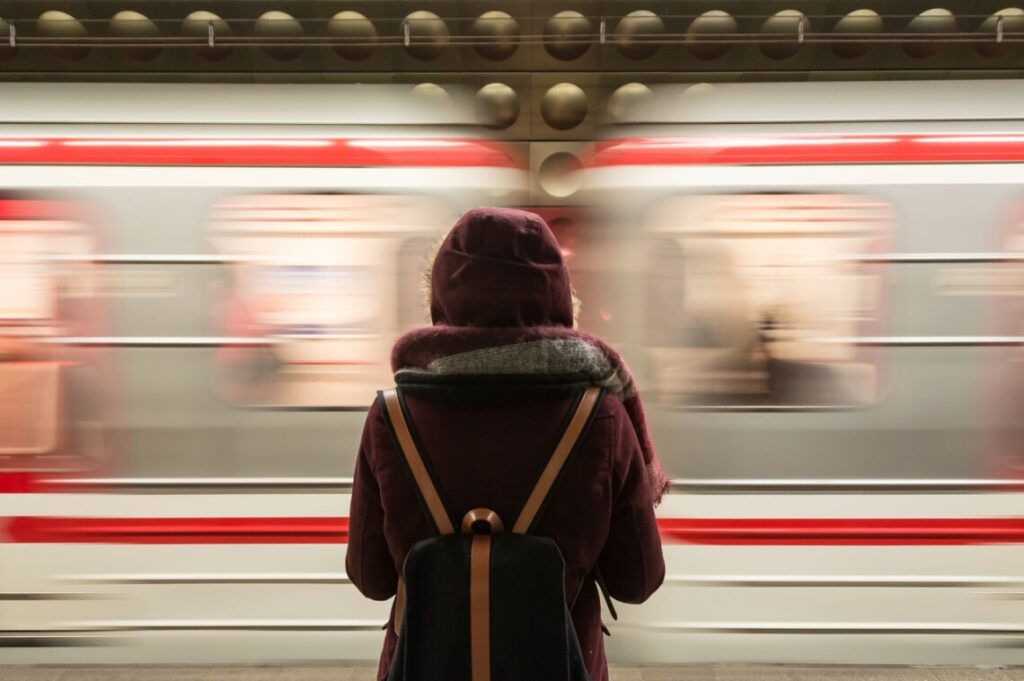 Woman wearing backpack standing in front of a blurry overnight train