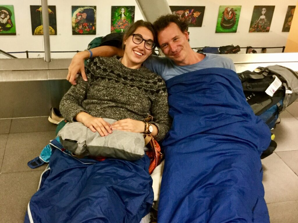 A woman and man (the owners of this blog) sit in sleeping bags on the floor of an airport with their trave backpacks. They're smiling at the camera