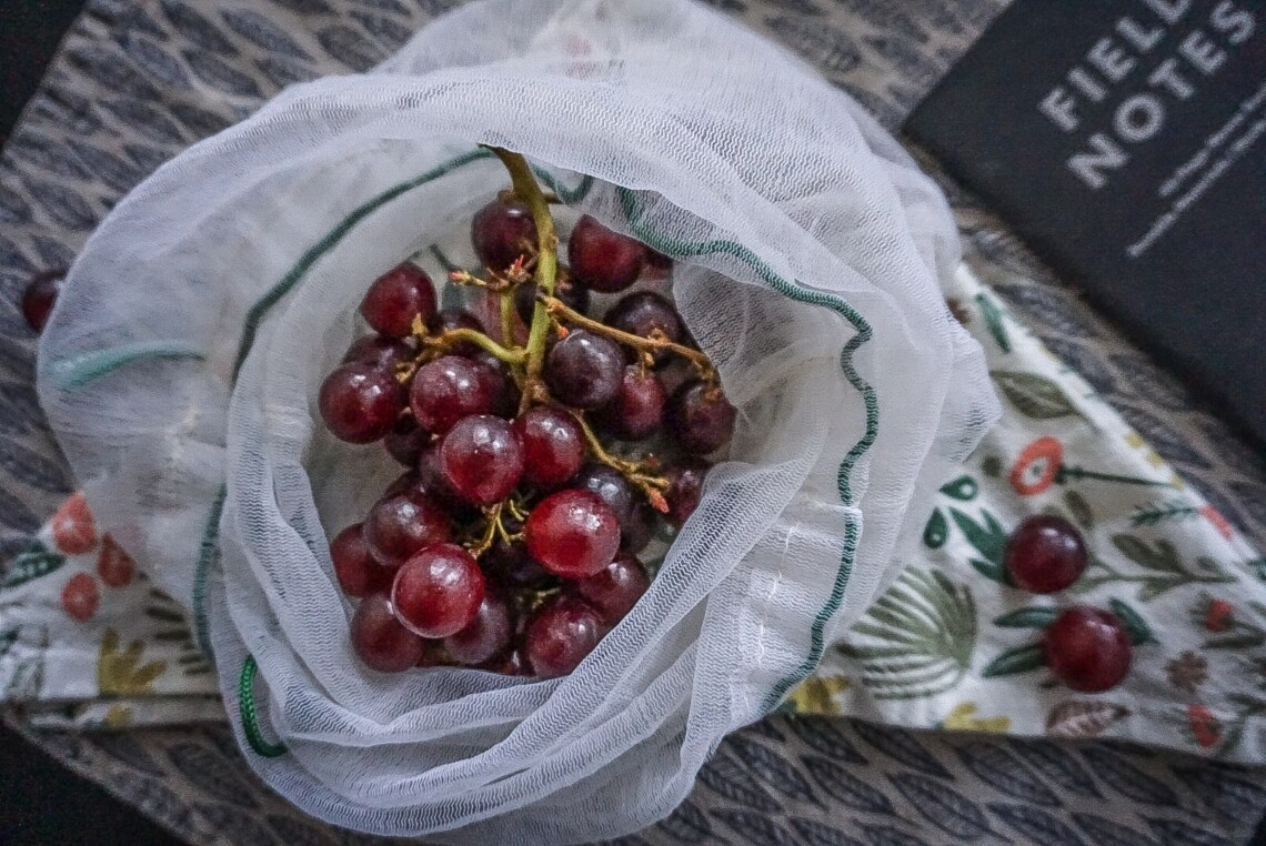 red grapes in a mesh produce bag on top of a napkin