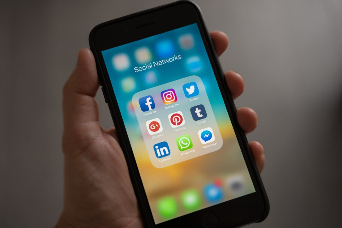a hand is holding a phone displaying social network apps, including Pinterest