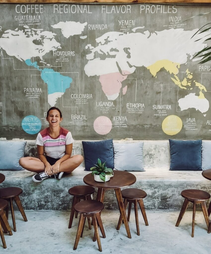 smiling woman on a bench with a map of coffee regions painted on the wall behind her