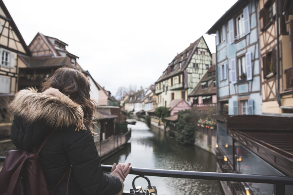 woman wearing a winter coat standing on a bridge in a traditional european town overlooking the river