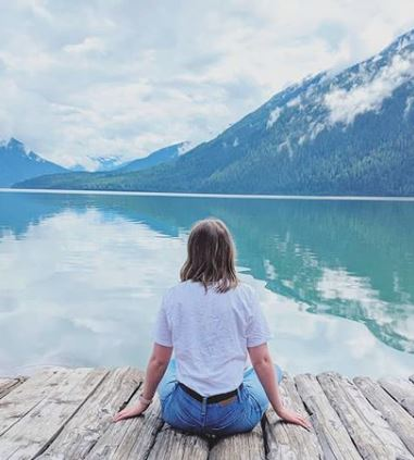 woman sitting on a dock with mountains in the background