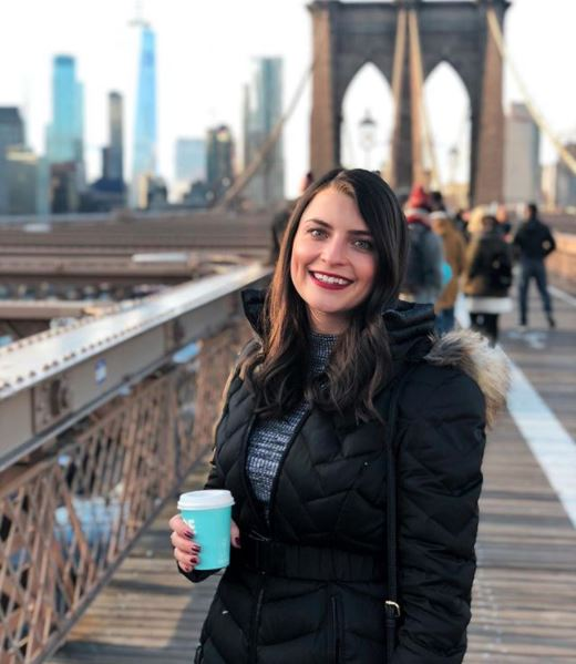 woman holding a cup of coffee while standing on a pedestrian bridge