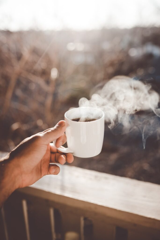 holding a steaming cup on a balcony