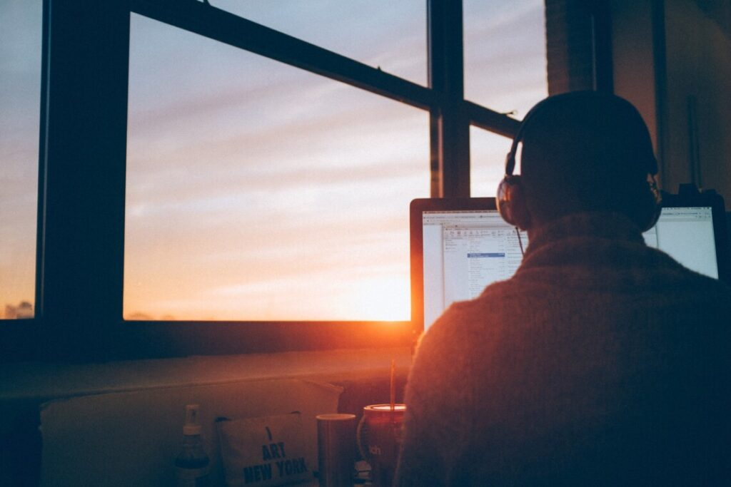 man working on his laptop at sunset
