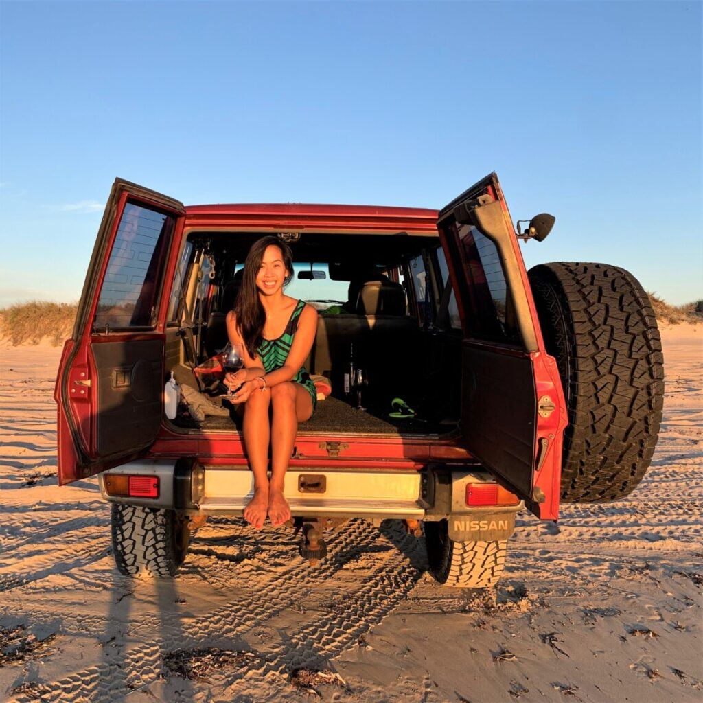 woman sitting in an opened backdoor of a red 4x4 on the beach