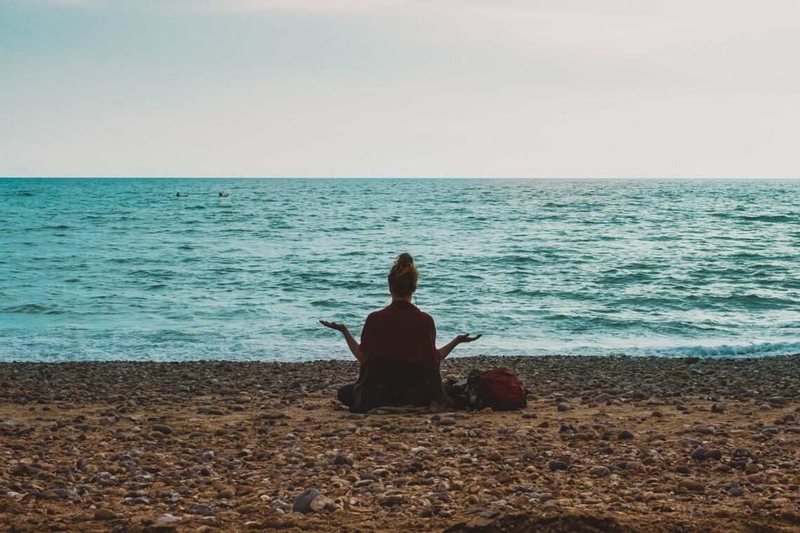 A woman sits on a beach with her back to the camera, with her arms shrugging