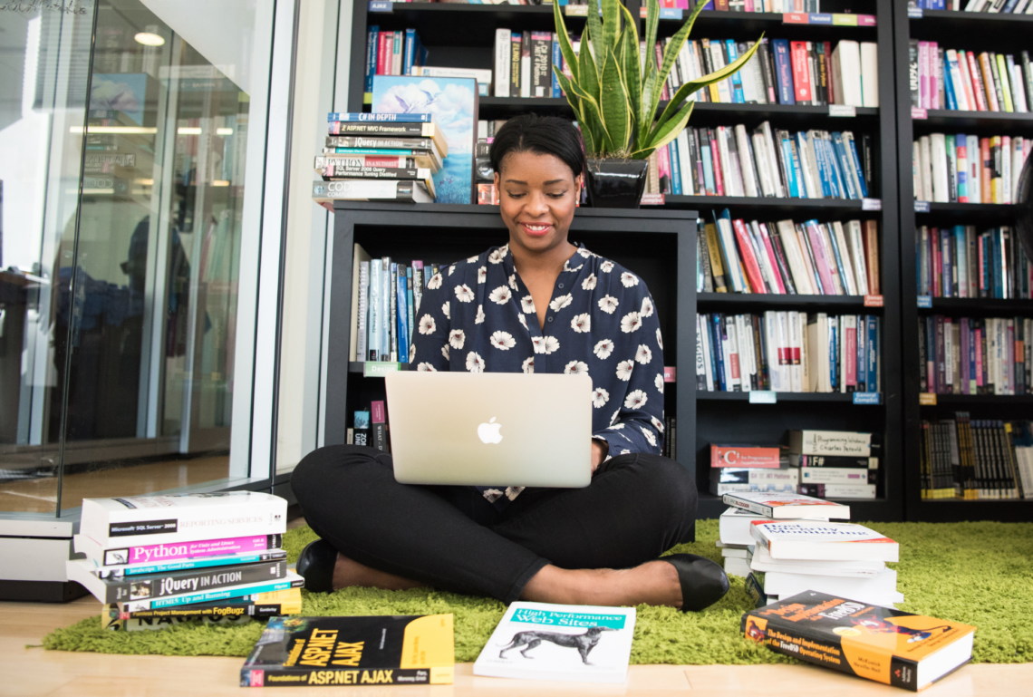 A Black woman sits on the floor in front of bookcases on her laptop, smiling, surrounded by books on the floor