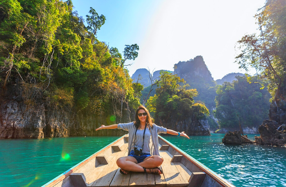 A woman sits at the front of a wooden boat, looking joyful, smiling at the camera with her arms stretched out to both sides. Behind her are tree-covered rock formations bursting out of the ocean.