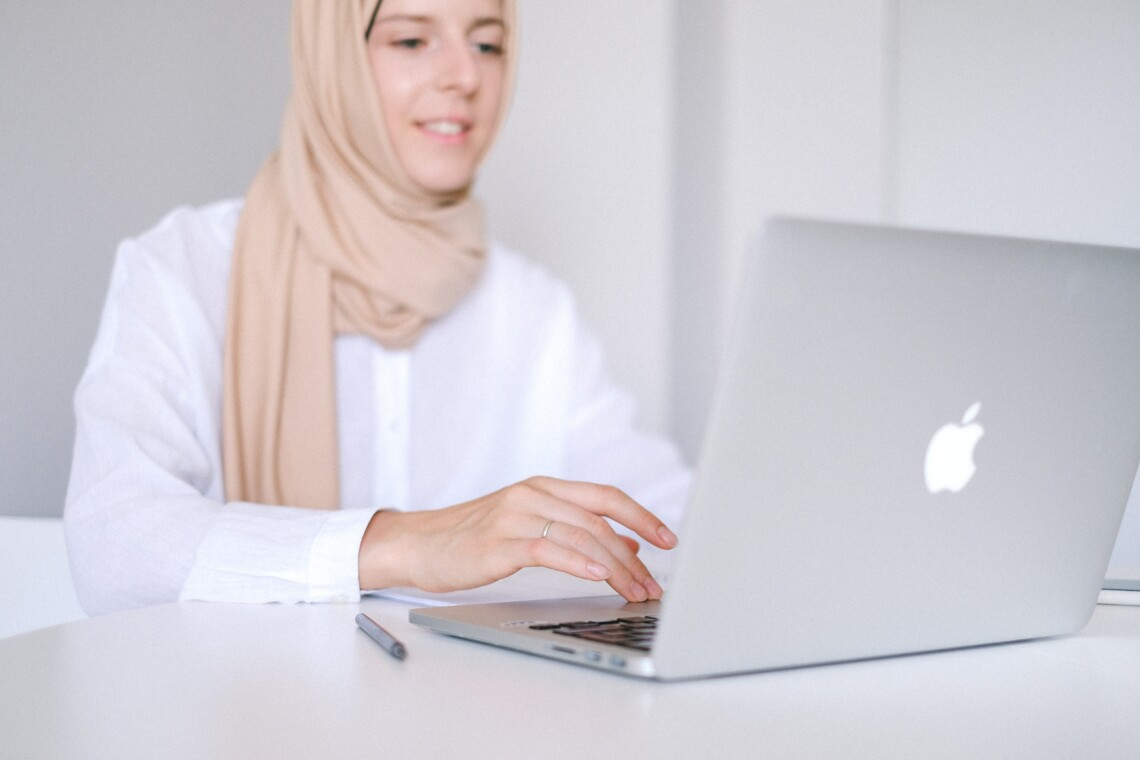 A woman wearing a hijab sits smiling at her laptop