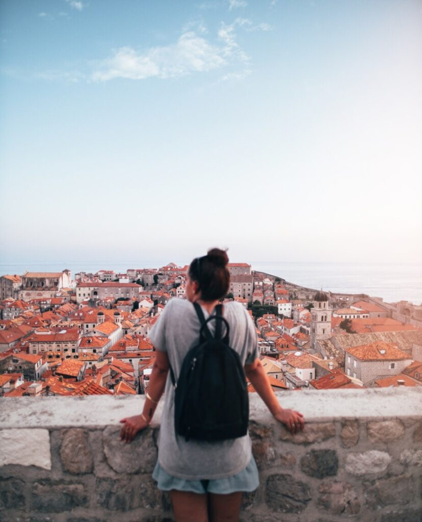 woman with backpack looking out over old european city