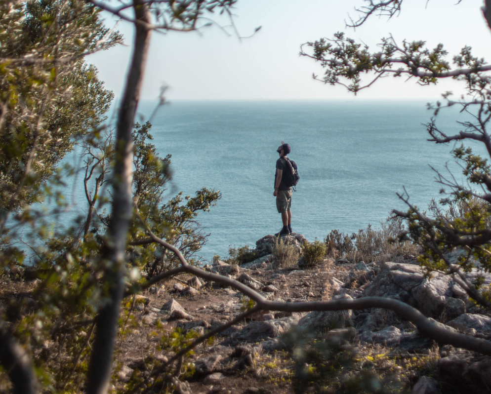hiker on a cliff looking at the sky