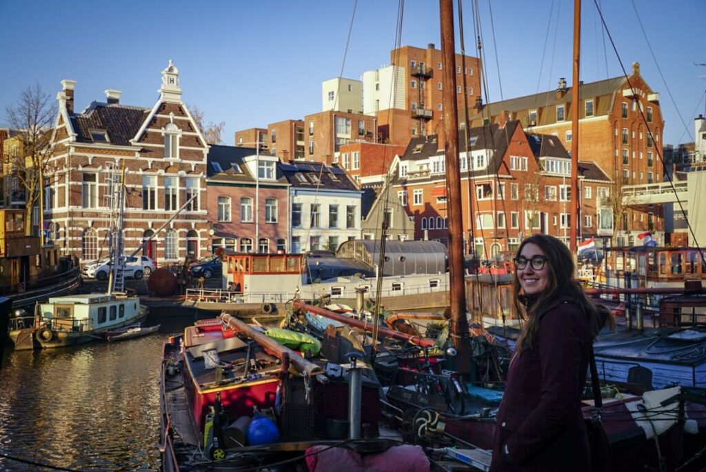 A woman (the owner of this blog) smiles at the camera in front of a Dutch canal covered in houseboats