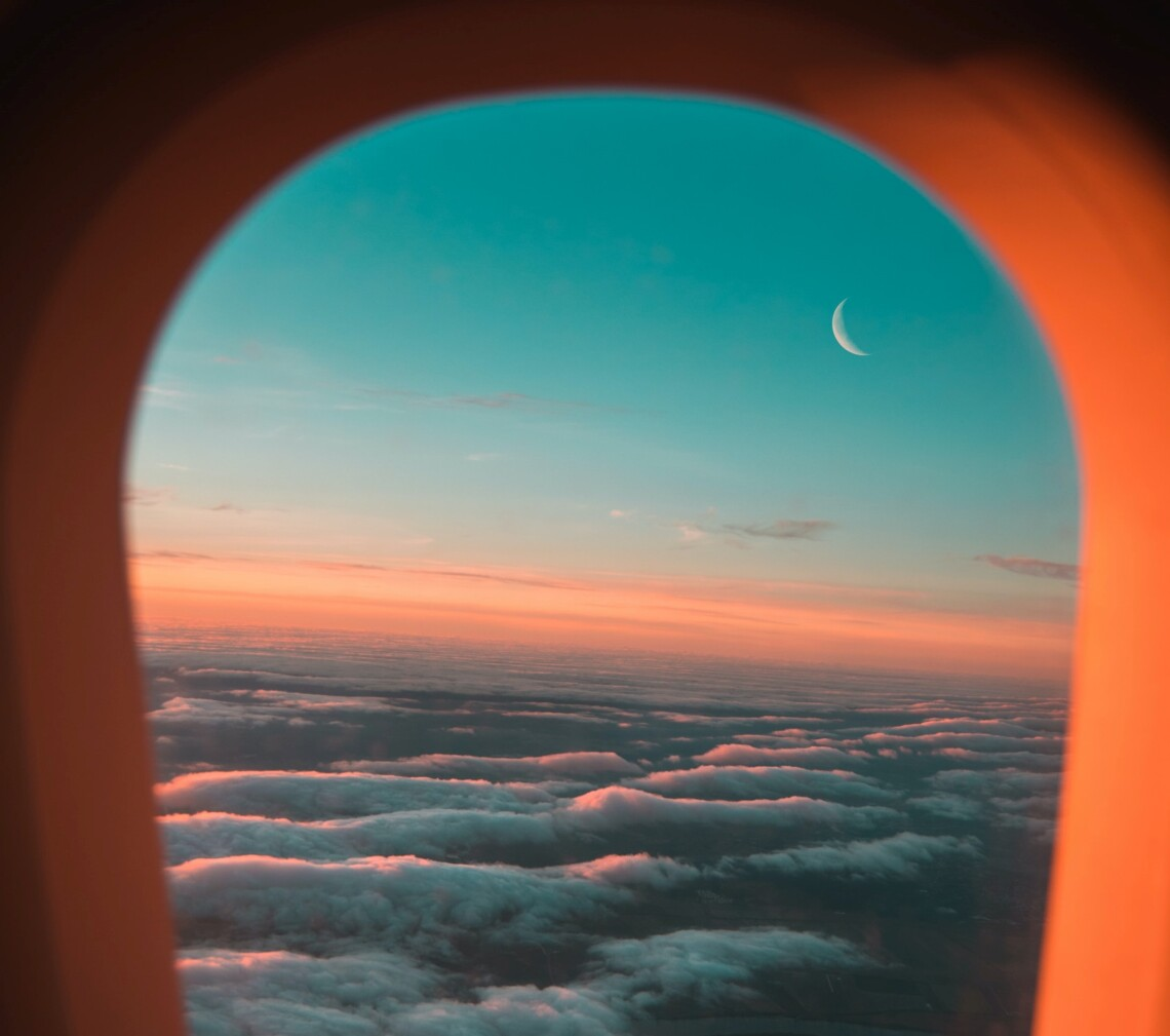 The view from an airplane window at sunset. The clouds and plane window are lit up pink from the sunset, and a crescent moon hangs above the clouds
