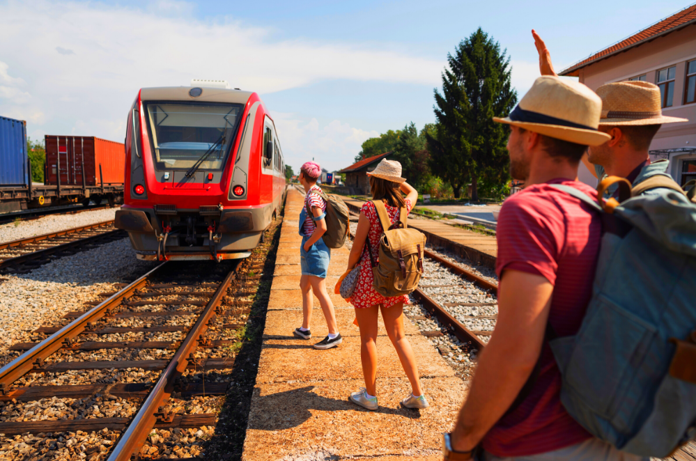 A group of people stand on the side of train tracks with backpacks on