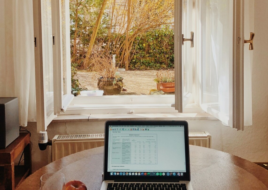 A laptop sits on a wooden table in front of an open window.