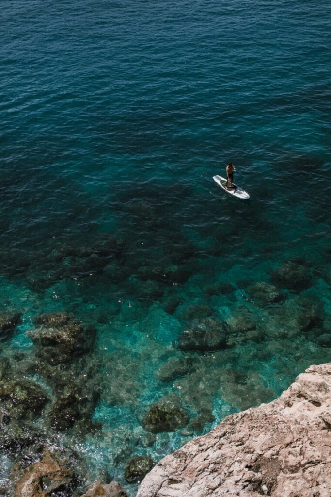 very clear water underneath a person standing on a surfboard