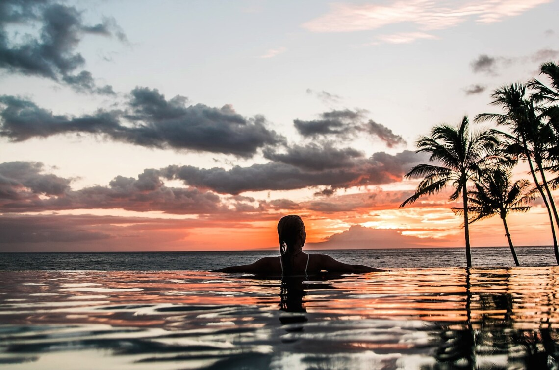 A woman sits in a swimming pool above the ocean with palm trees and a sunset in the background