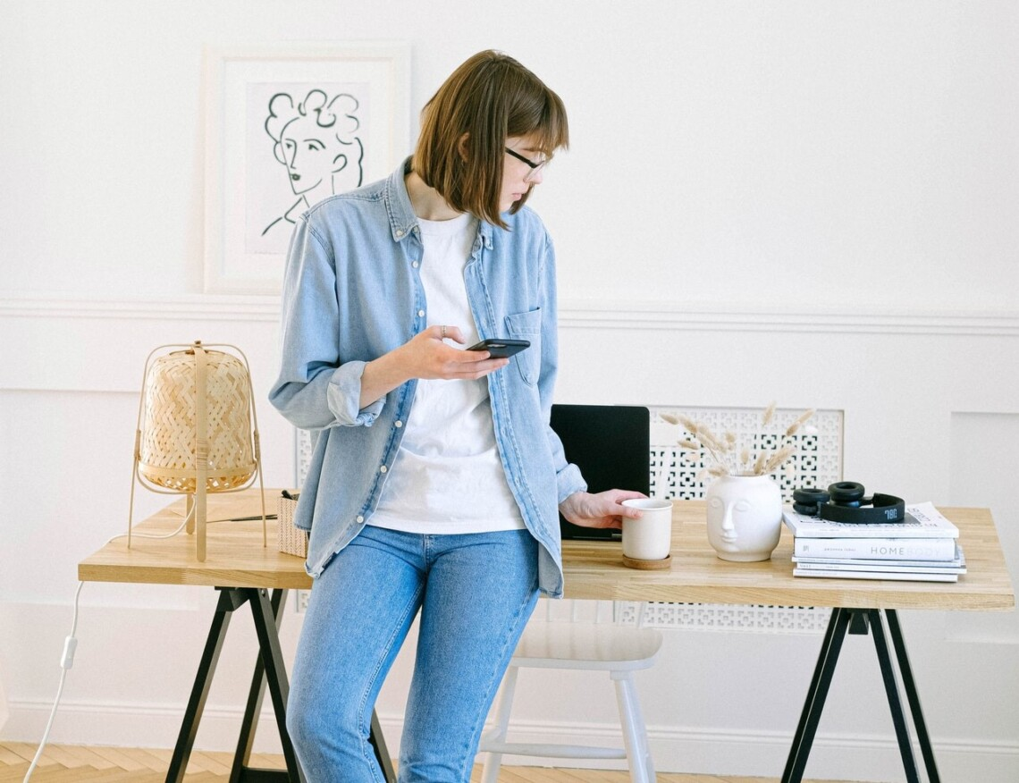 A woman sits on top of a wooden desk with a cup of coffee, with her phone in her hand