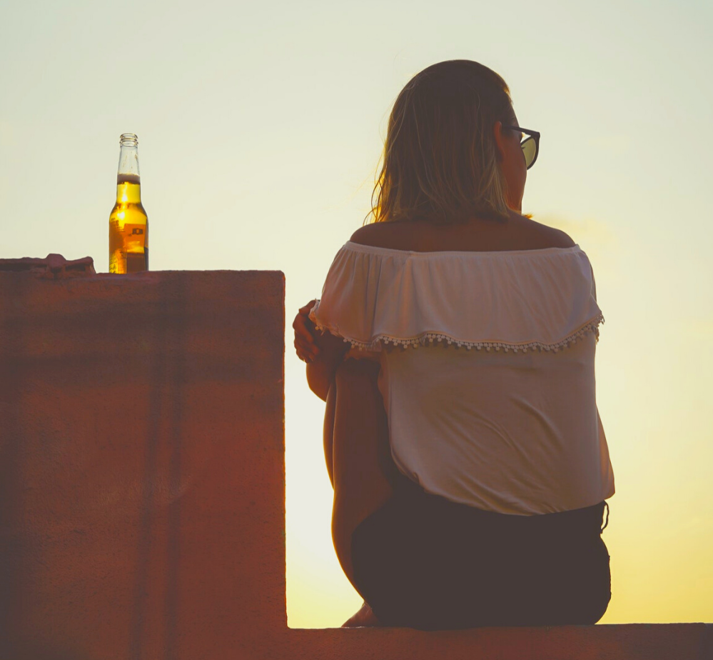 A woman sits on a ledge, facing away from the camera at sunset. There is a beer next to her. She looks thoughtful