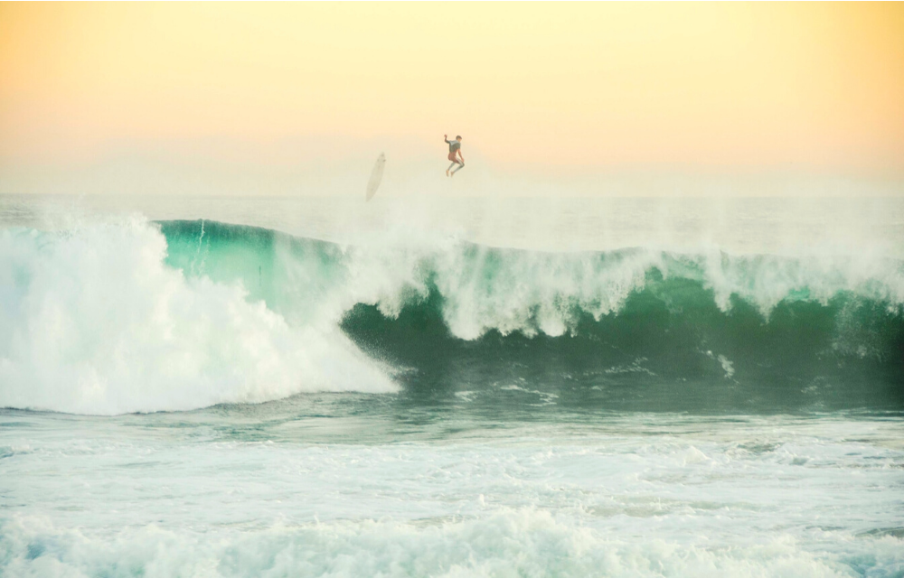A dreamy photo of someone surfing. A pastel sky is behind the crashing waves, and the surfer has jumped off of their board from the top of the wave. It looks like freedom