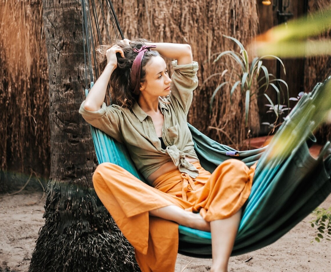 A woman sits in a hammock looking off into the distance. There are palm trees blurred in the foreground.