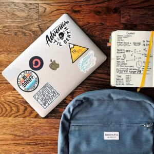 A notebook, a backpack and a Macbook covered in stickers sit on a wooden table