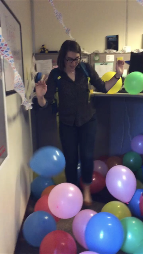 A woman (the owner of this blog) stands in a cubicle that is filled with balloons. She is laughing and dancing in the balloons wearing business clothes and a backpack