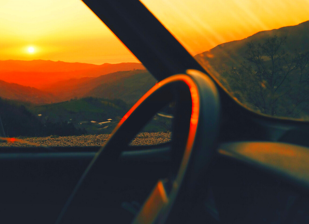 View from the passenger seat of a car at sunset. Bright red colors of sunset outline mountains and steering wheel of car, giving feeling of adventure.