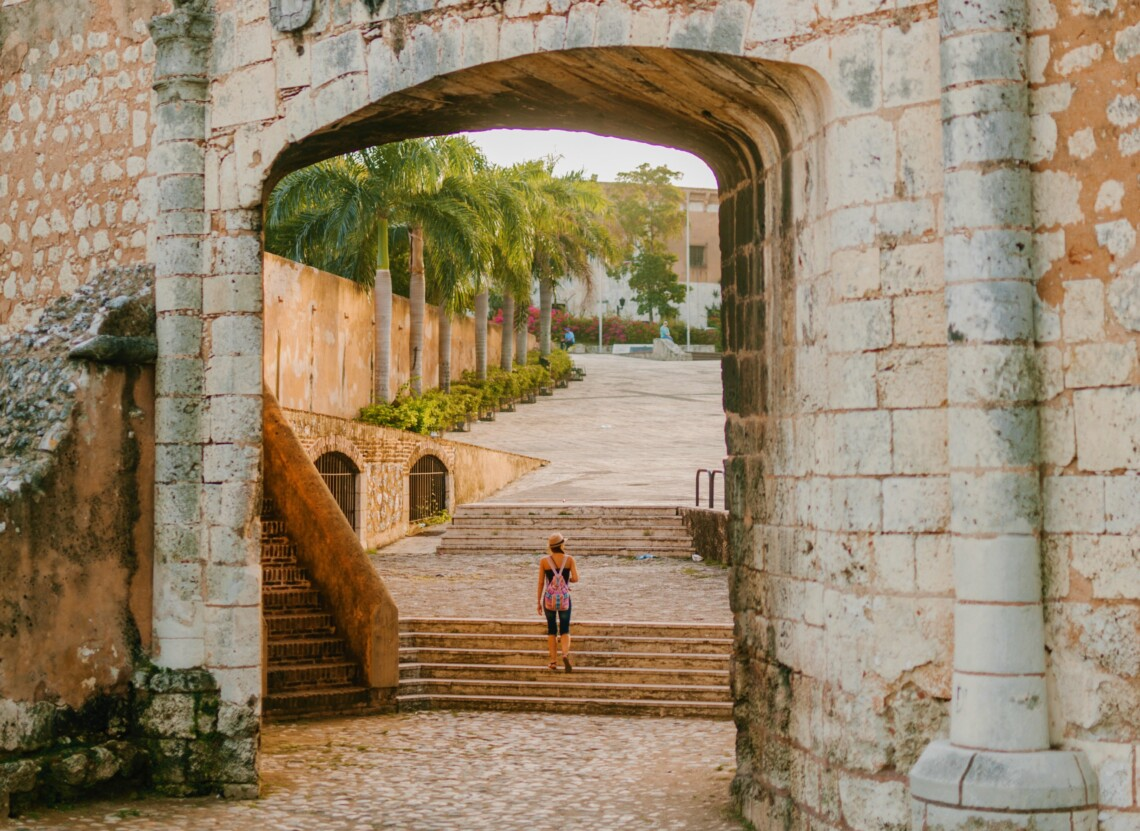 A woman walks underneath of an old, aged stone archway up steps. There are palm trees in the background and the image inspires adventure and travel.