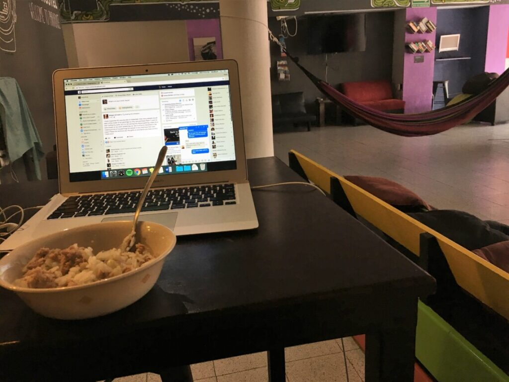 An open laptop sits on top of a table with a bowl of food next to it. In the background, there is a hammock and colorful purple walls
