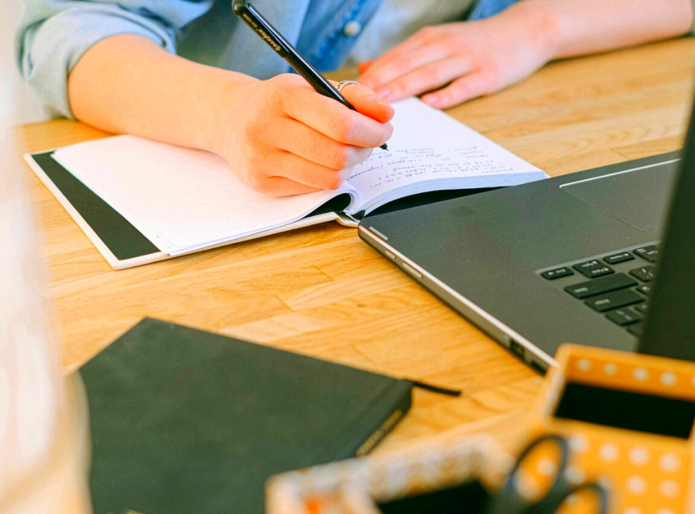 A woman's hands are seen writing in a notebook at a busy desk