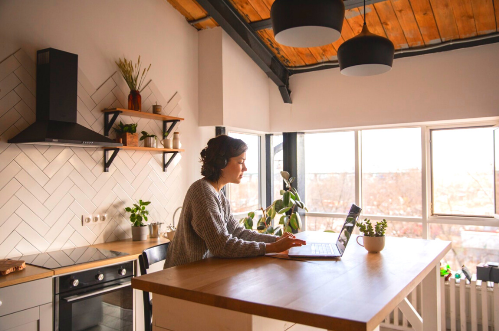 woman working at kitchen table on laptop