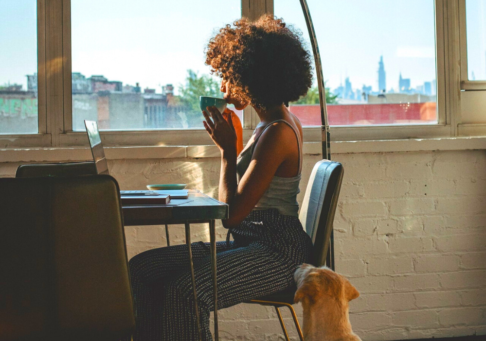 A Black woman sups a coffee cup in her pajamas at her laptop with a city skyline outside of the window behind her
