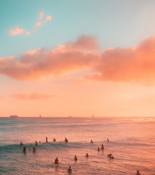 Surfers sit on the surf boards waiting for a wave. The water and sky are a beautiful pink and blue, very dreamy