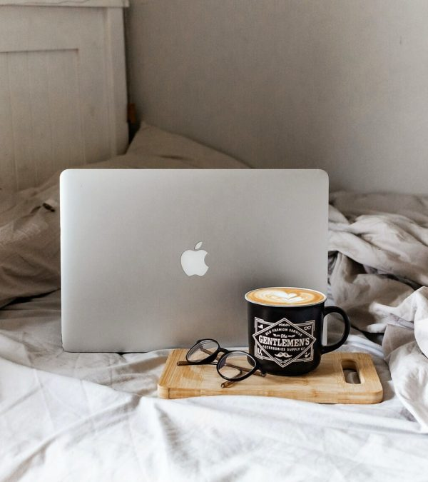 On a white bed sits a Macbook, a wood cutting board, a pair of glasses and a coffee mug